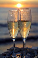 Two glasses of sparkling wine in the sunset at the sea