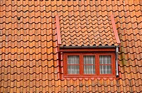 Attic with red window in old tile roof. Jutland, Denmark