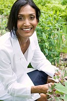 Ethnic woman in white lab coat holding plant in garden