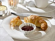 Breakfast table place setting with a croissant and jam