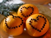 Oranges with a heart pattern made of cloves