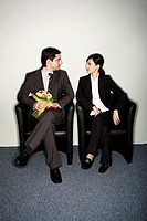Male office worker with flowers sitting next to female colleague