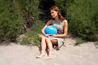 Businesswoman on beach with globe (thumbnail)