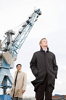 Two businessmen underneath a crane