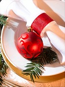 Place cover with a white napkin, a red Christmas tree ball and a fir branch