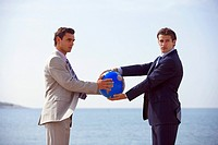 Businessmen on beach holding globe (thumbnail)