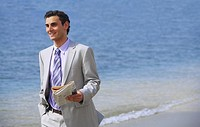Businessman on beach holding a newspaper