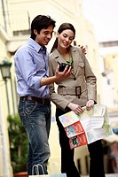 Couple with map looking at digital camera