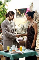 Businessman and businesswoman in garden cafe shaking hands (thumbnail)