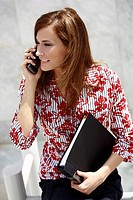 Businesswoman on cell phone holding a binder