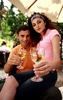 Woman sitting on man's lap holding glasses of wine (thumbnail)