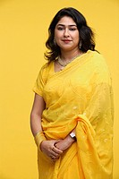 Woman in yellow sari standing against yellow background