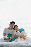 Couple sitting on bed, eyes closed