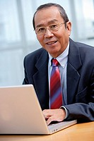 Businessman with laptop, smiling at camera
