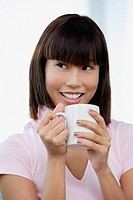 Young woman holding mug, smiling