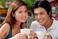Couple in cafe having coffee, smiling at camera