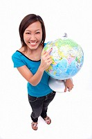 Woman holding globe, smiling at camera