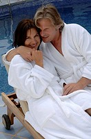 Couple at the swimming pool in a bathrobe