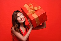 Woman in red dress, holding wrapped gift box