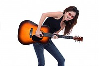 Young woman playing guitar, studio shot