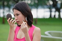 Young woman outdoors, looking at compact, applying make-up