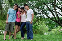 Young adults standing in park, smiling at camera