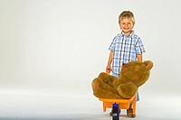 Portrait of a boy pushing a wheelbarrow with a teddy bear in it