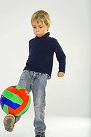 Boy balancing a ball on his leg