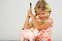 Close-up of a girl breaking a piggy bank with a hammer and smiling