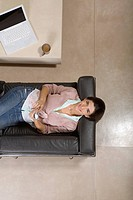 View from above of woman laying on couch smiling