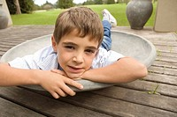 Young boy relaxing on outdoor deck