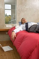 Businessman lying in bed relaxing