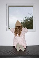 Young girl looking out window