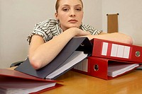 Portrait of a young businesswoman leaning over files