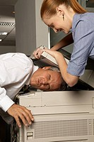 Businesswoman pressing the head of a businessman under a photocopier