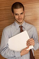 Portrait of a businessman holding a laptop