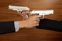 Hands of two businessmen pointing guns at each other