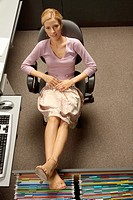 Young woman sitting in an office chair with her legs on a filing cabinet drawer