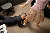 High angle view of a businessman grabbing his colleague's leg