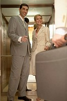 Three businesspeople standing in a corridor