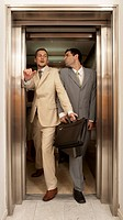 Two businessmen struggling to get out of an elevator