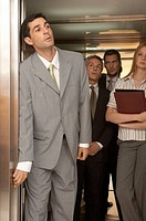 Businessman looking outside of an elevator with his colleagues standing behind him