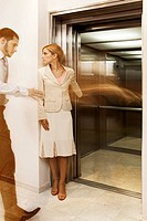 Businessman and a businesswoman standing in front of an elevator