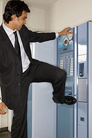 Businessman hitting a vending machine with his leg (thumbnail)