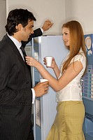 Side view of a businessman and a businesswoman standing in front of a vending machine