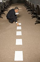 Side view of a businessman crouching and picking up papers