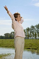 Woman Outdoors lifting arms up in freedom