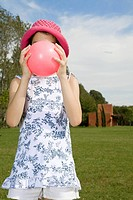Girl holding pink ball in front of face