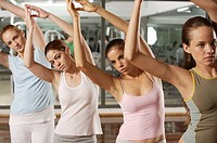 Four young women doing yoga in a gym