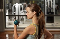 Side profile of a young woman exercising with a dumbbell (thumbnail)